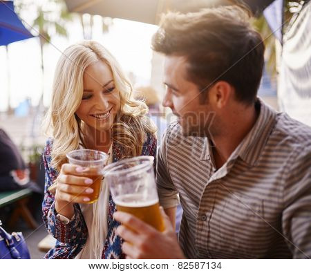 romantic couple drinking beer in plastic cups at outdoor bar