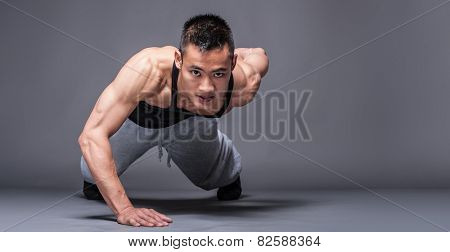Young asian man workout over grey background - one handed push-up