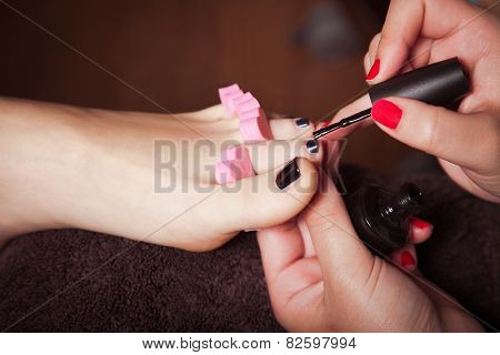 woman at cosmetics salon applying black  nail polish on toenails
