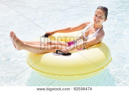 Happy Woman Relaxing On Inner Tube In Swimming Pool