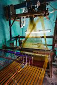 Man weaving silk sari on loom. in Kanchipuram, Tamil Nadu, India. Kanchipuram is famous for hand woven silk sarees and most of the city's workforce is involved in  weaving industry poster