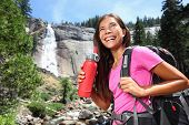 Healthy hiker girl drinking water in nature hike. Beautiful young woman hiking happy with water bottle in front of Vernal Fall, Yosemite National Park, California, USA. poster