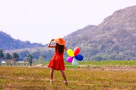 Young Woman With Balloons On The Meadow