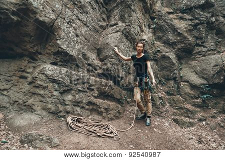 Beautiful young climber woman standing near the stone rock outdoor poster