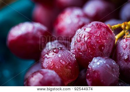 Closeup image of red grape covered in water drops