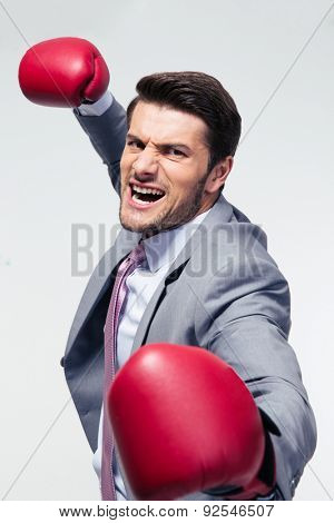 Angry businessman with boxing gloves over gray background