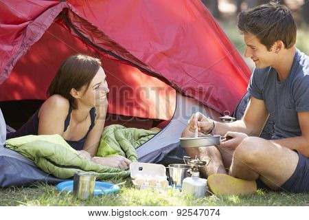 Young Couple Cooking Breakfast On Camping Holiday