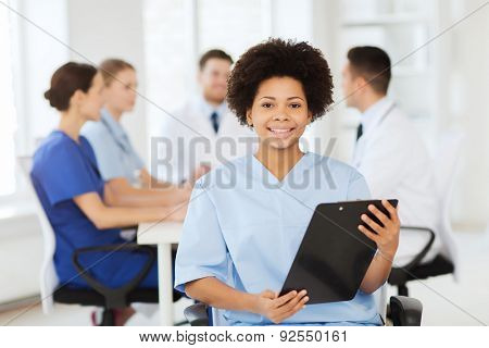 clinic, profession, people and medicine concept - happy female doctor or nurse with clipboard over group of medics meeting at hospital poster