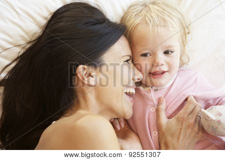 Mother And Daughter Relaxing In Bed