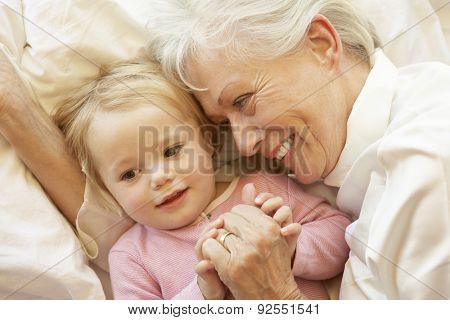 Grandmother Cuddling Granddaughter In Bed