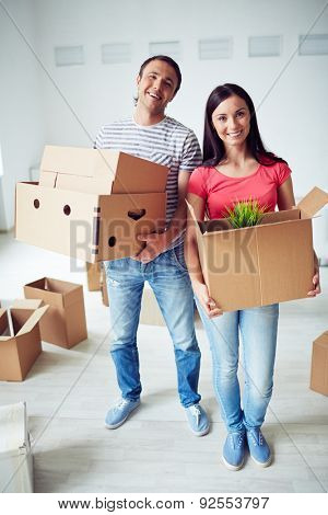 Happy settlers with packages standing in their new house
