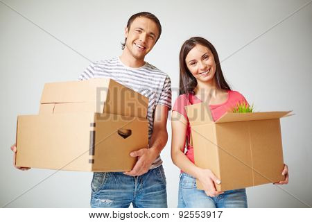 Happy settlers holding packages with domestic things