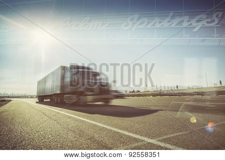 California desert trucking double exposure image - Truck on Highway i10 passing through Palm Springs Mohave desert area sun blazing down on asphalt road.