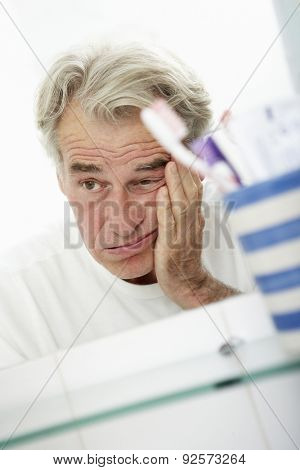 Tired Senior Man Looking At Reflection In Bathroom Mirror