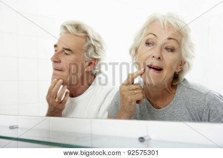Senior Couple Looking At Reflections In Mirror For Signs Of Ageing