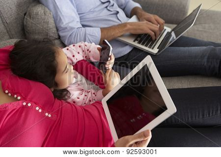 Family On Sofa With Smartphone, Laptop And Digital Tablet