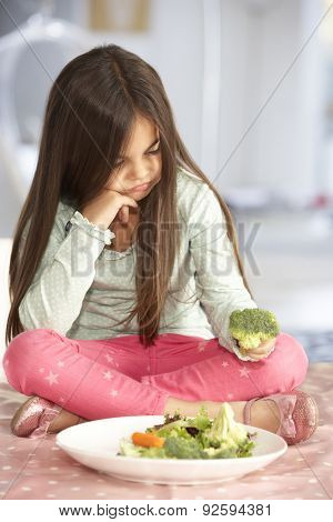 Unhappy Young Girl Rejecting Plate Of Fresh Vegetables
