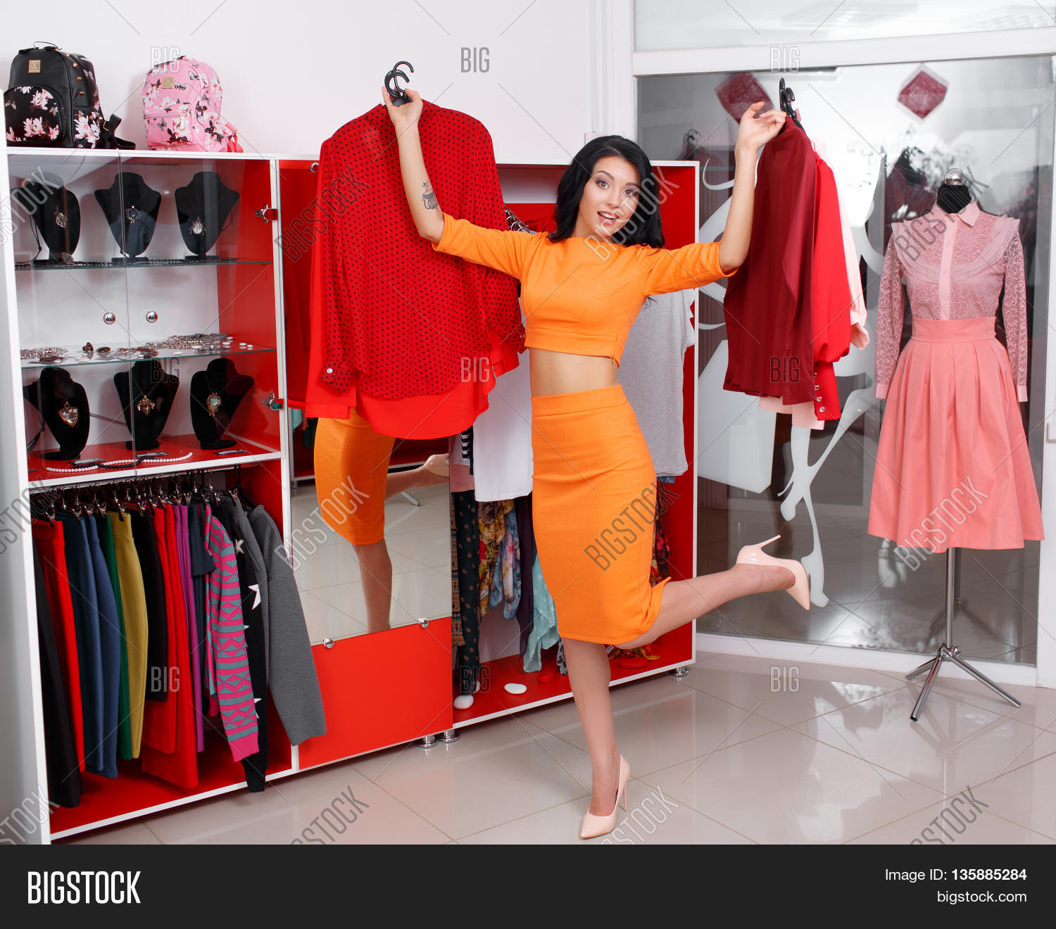 3db6569faebfc Young woman shopping in a clothing store. Woman shopping for dress in  clothing retail store