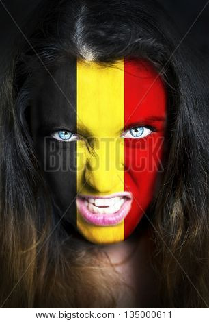 Portrait of a woman with the flag of the Belgium painted on her face.