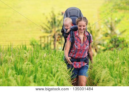 Nature walk in green rice terrace field. Happy mother hold little traveller in carrying backpack. Baby ride on woman back. Travel adventure hiking with child carrier family summer vacation on Bali.