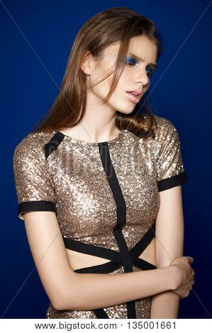 Young woman in a golden shining dress studio portrait. Fashion style, dark blue background.