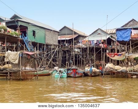 traditional settlement with wooden houses at the Tonle Sap river in Cambodia poster