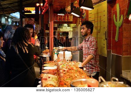 LONDON - OCTOBER 04: Unidentified people trade food in Camden Town market on October 04 2014 in London UK. Camden Town markets are visited by 100000 people each weekend