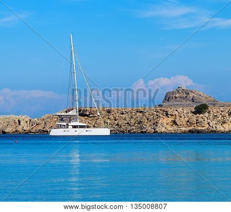 boat on a mooring on a background of rocks in the Bay of Lindos, Aegean Sea
