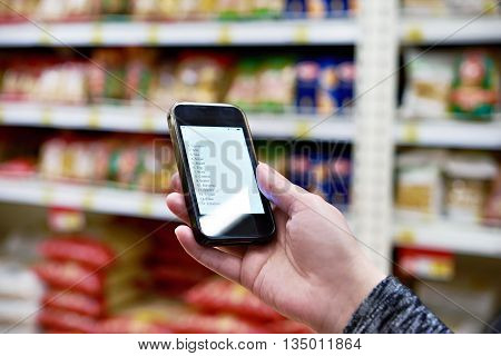 Shopping List On Smartphone Screen In Hand Of Women Customers