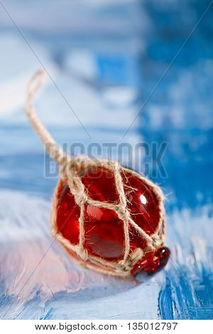 red Glass float on blue painted background