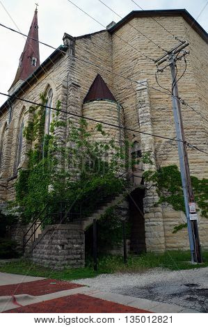 The back stairway and door to the abandoned Saint Mary Carmelite Church in downtown Joliet, Illinois. The stairway is blocked by overgrown trees and vines.