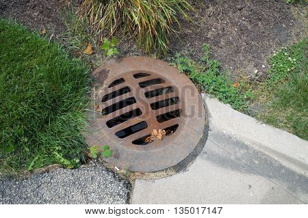An iron storm drain cover allows storm water to drain away in the corner of a parking lot in Shorewood, Illinois.