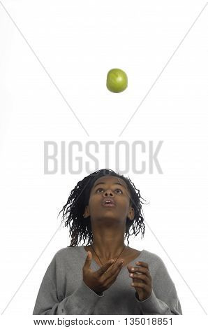 Teenage girl jugglery an apple on white background