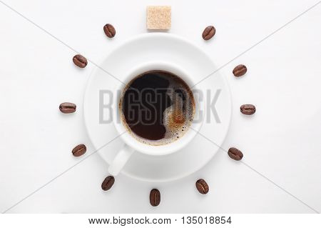 Cup of coffee with foam on saucer and coffee beans with cane sugar cube against white background forming clock dial viewed from above