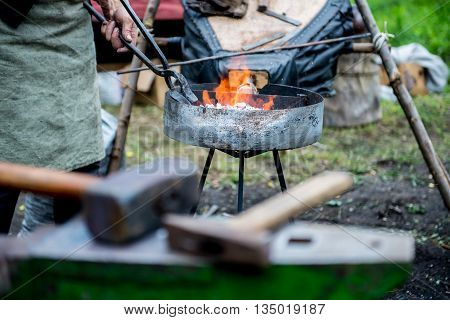blacksmith forges detail. Blacksmith working outdoors. Master works on the anvil.
