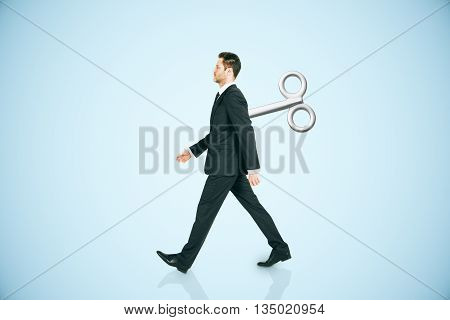 Walking businessman with a wind-up key on his back walking on blue background. Concept of control