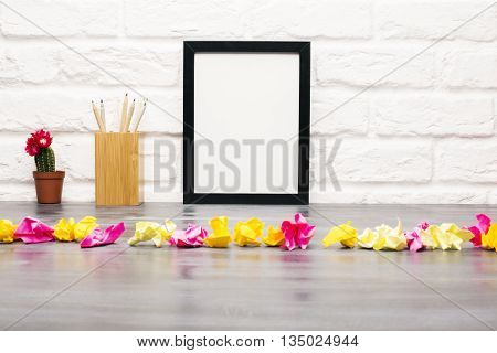 Closeup of messy dark wooden table with blank picture frame cactus pencils and row of crumpled paper pieces on white brick wall background. Mock up
