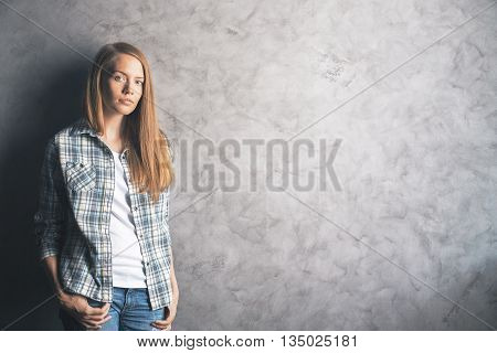 Casually dressed beautiful young woman standing against blank concrete wall. Mock up