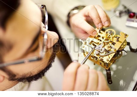Close up portrait of a watchmaker at work. He is wearing specialist magnifying glass.Old pocket watch being repaired by watch maker.Selective focus on watch.
