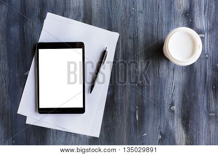 Top view of blank white tablet paper sheets pen and take away coffee cup on dark wooden desktop. Mock up