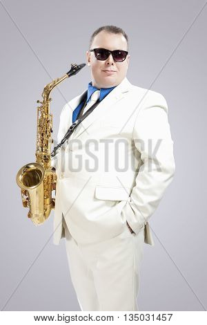Handsome Smiling Male Saxo Player in Stylish White Suit and Sunglasses Posing Against White Background. Vertical Image Orientation