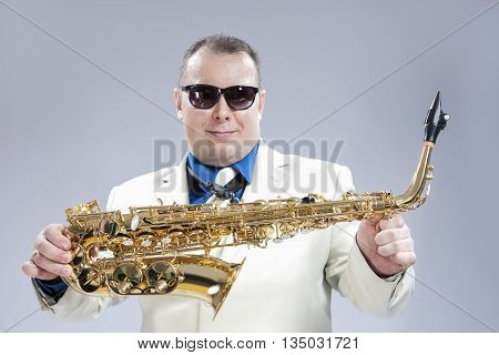 Smiling Happy Male Saxo Player in White Suit and Sunglasses Posing with Saxophone Against White Background.Horizontal Image Composition