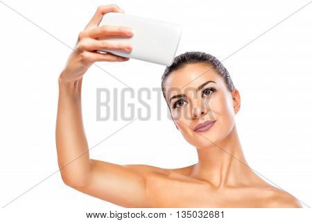 Young woman taking a self photo.Head and shoulders portrait of beautiful model on white background.