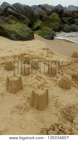 Sandcastles upon beach seascape photographed at Hopton On Sea in Norfolk