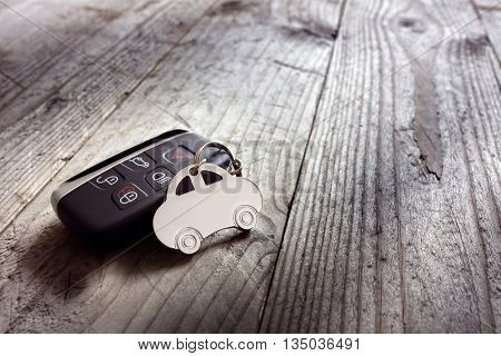 Car shape keyring and keyless entry remote on wood background