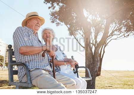 Relaxed Senior Couple Sitting On A Park Bench