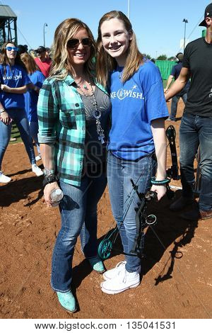 ARLINGTON, TX - APR 18: TV personality Kristy Titus (L) poses with a Make A Wish member at the ACM & Cabela's Great Outdoor Archery Event at the Texas Rangers Youth Ballpark on April 18, 2015.