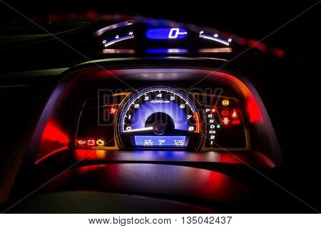Modern car instrument dashboard panel and digital speed meter in night time