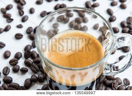Hot espresso shot with soft crema in the clear glass on the roasted coffeselect focus.