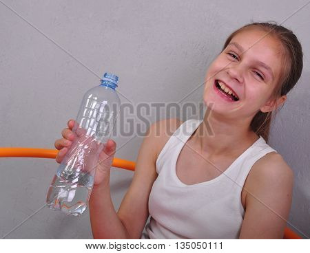 Outdoor portrait of a sportive child inline skating in the park and drinking water from bottle. Childhood sports active lifestyle concept.